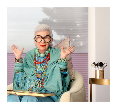 Iris Apfel, in a commercial for Hunter Douglas, wearing big round glasses and PowerView motorized window treatments behind her.