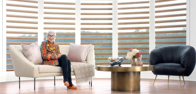 Lady with big glasses, sitting on a couch, with PowerView motorized window treatments by Hunter Douglas behind her.