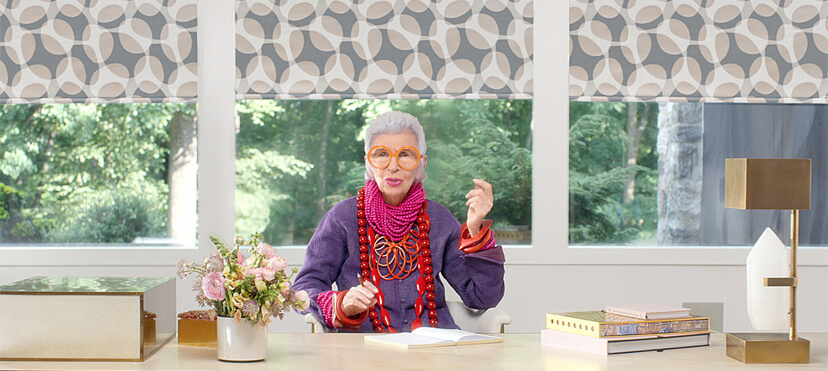 Iris Apfel, wearing big glasses, sitting behind a desk with PowerView motorized window shades by Hunter Douglas behind her.